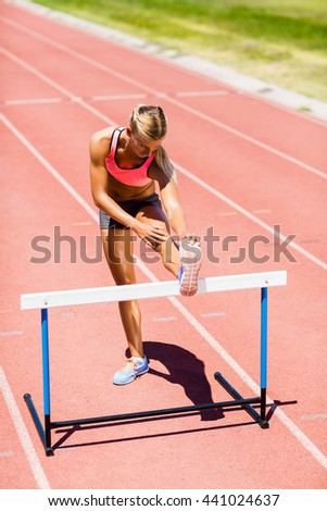 Female athlete warming up on running track on a sunny day - stock photo