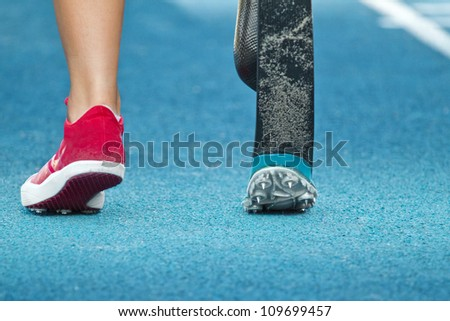 female athlete with handicap prepares for long jump - stock photo