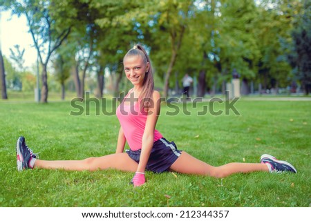 female athlete working out in the park, stretching and running - stock photo
