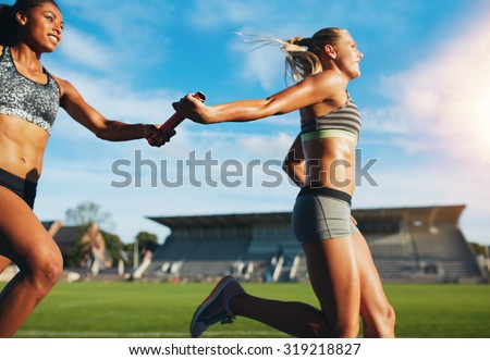 Female athletes passing over the baton while running on the track. Young women run relay race, track and field event. - stock photo