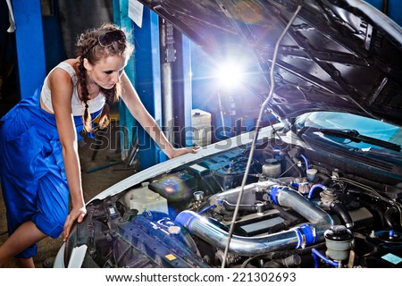 Female auto mechanic repairing a car, working on the transmission. - stock photo