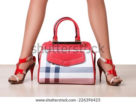 Female bag between beautiful woman's legs in sandals - stock photo