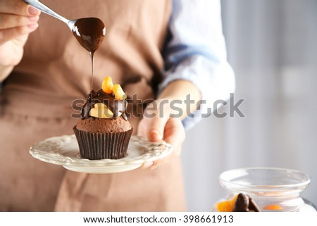Female baker decorating tasty cupcake with slice of mandarin and chocolate on the table - stock photo