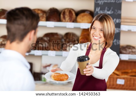 Female baker giving coffee and croissant to male customer in the bread store - stock photo