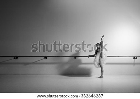 Female ballerina posing in white tutu and ballet shoes. Grayscale image. - stock photo