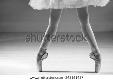 Female ballerina standing on toes in ballet shoes, low section. Grayscale image. - stock photo