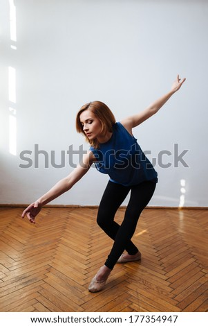 Female ballet dancer stretching her arms in a balanced move - stock photo
