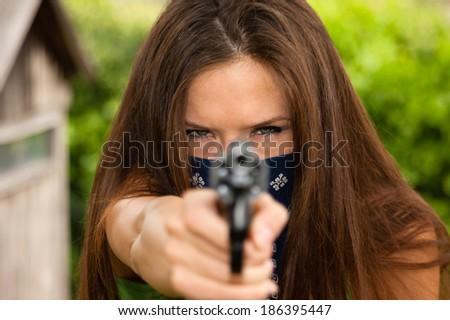 Female Bandit Points Snub Nose Revolver Handgun Weapon - stock photo