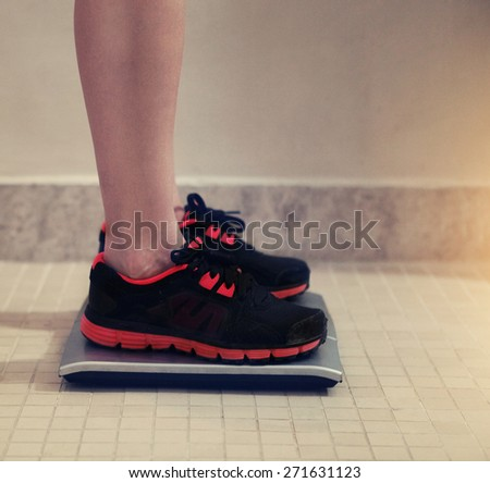 Female bare feet with weight scale in the sport gym - stock photo