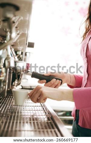 Female barista making coffee with an espresso coffee machine - stock photo