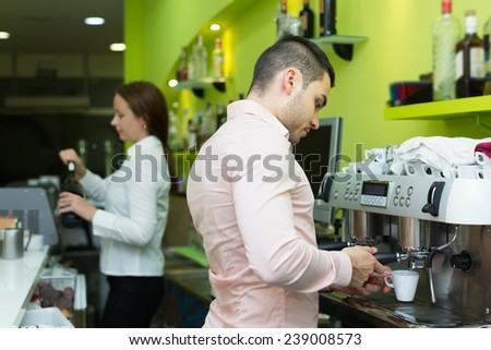 Female bartender and young male barista working at bar together. Focus on man  - stock photo