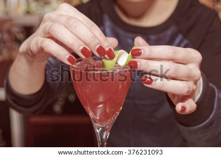 Female bartender is adding lime zest to cocktail, toned image - stock photo
