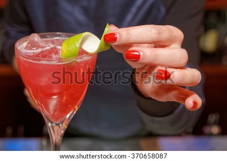 Female bartender is decorating a cocktail with lime zest - stock photo