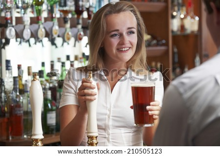 Female Bartender Serving Drink To Male Customer - stock photo