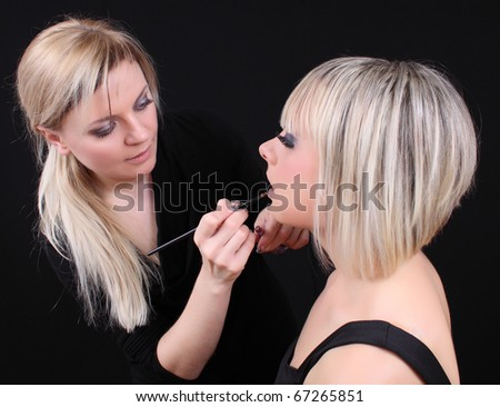 female beautician makes makeup lips - stock photo