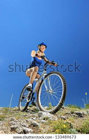 Female biker biking a mountain bike outdoor - stock photo
