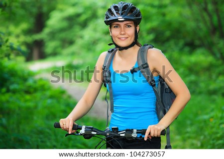 Female biker in a park. - stock photo