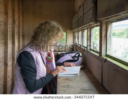 Female Bird Watcher  identifying birds in a book - stock photo