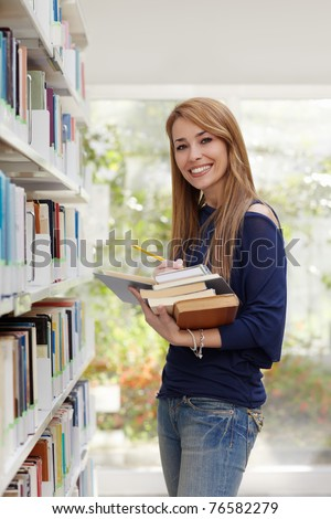 female blonde college student taking book from shelf in library and looking at camera. Vertical shape, side view, waist up - stock photo