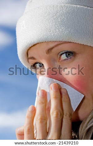 Female blowing her nose (blue sky background) - stock photo