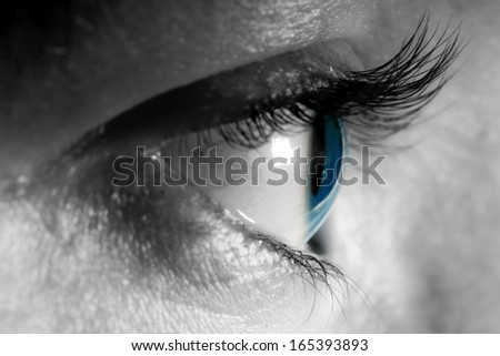 Female blue eye close-up, natural light. Side view. - stock photo