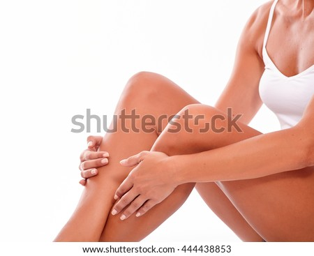 Female body with knees bent sitting down and holding hands on calves while wearing a white tank top on a white background - stock photo