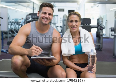 Female bodybuilder sitting with personal trainer smiling at camera at the gym - stock photo