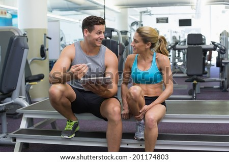 Female bodybuilder sitting with personal trainer talking at the gym - stock photo