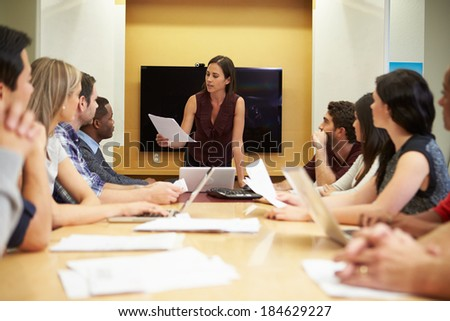 Female Boss Addressing Meeting Around Boardroom Table - stock photo