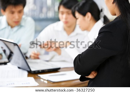 Female boss watching her employees working in the office - stock photo
