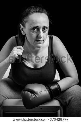 Female boxer sitting after training. Black and white portrait. - stock photo