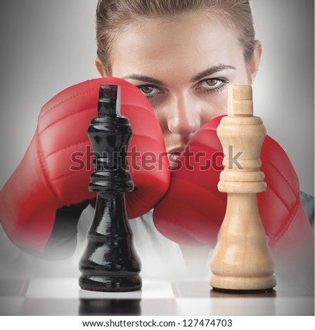 Female boxer with fists raised behind the chess board - stock photo