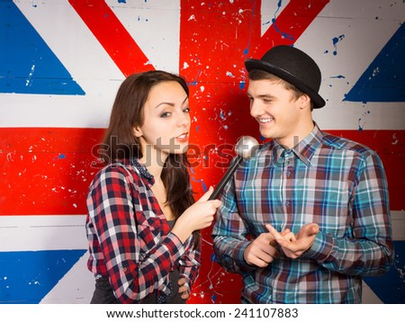 Female British chat show host interviewing a handsome young man in a bowler hat in front of a Union Jack flag painted on the wall - stock photo