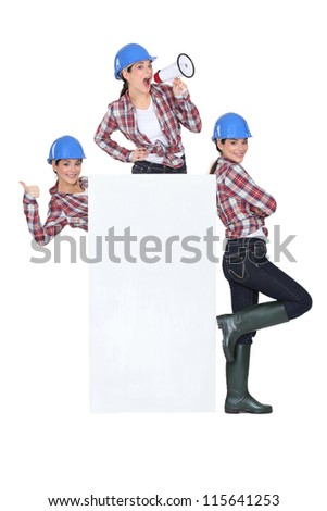 Female builder with megaphone and poster - stock photo