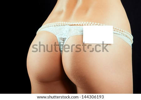 Female bum in white panties and empty name tag in studio on black background - stock photo