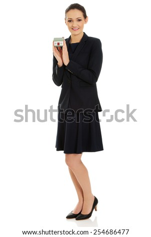 Female business agent holding house model. - stock photo