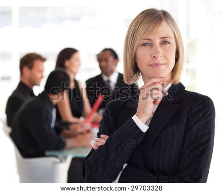 Female Business leader standing in front of her team - stock photo