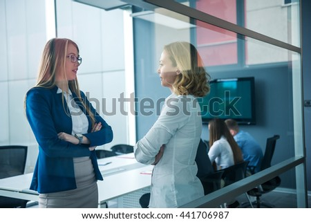 Female business partners talking about work in an office. - stock photo