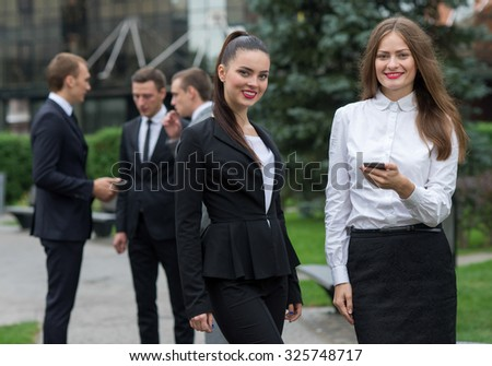 Female business success. Portrait of two motivated business women. Successful women in formal wear at work. Their motivated colleagues are on the background. Outdoor business concept - stock photo