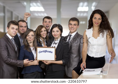 Female business trainer in front of the happy graduates who successfully passed the course.  - stock photo