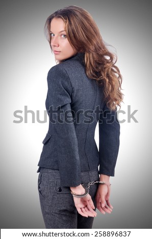 Female businesswoman with handcuffs on white - stock photo