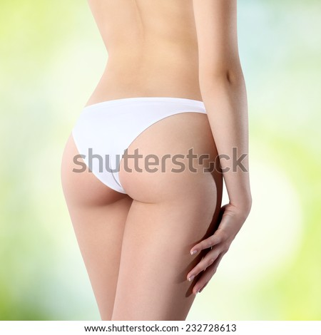 female buttocks in white panties on a green background - stock photo