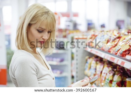 Female Buying Groceries At Supermarket - stock photo