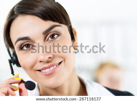 Female call center service operator at work. Portrait of smiling pretty female helpdesk employee with headset at workplace. Effective and efficient business information, help and support concept - stock photo