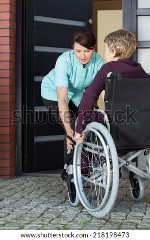 Female caregiver helping disabled woman on wheelchair entering home - stock photo