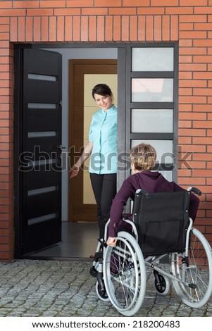 Female caregiver inviting elderly woman on wheelchair to nursing home - stock photo