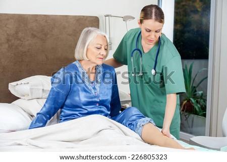 Female caretaker examining senior woman's leg in bed at nursing home - stock photo