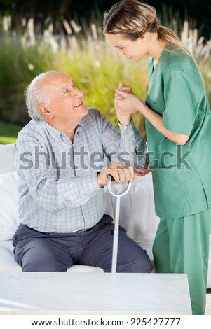 Female caretaker helping elderly man to get up from couch at nursing home - stock photo