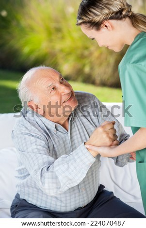 Female caretaker helping senior man to sit on couch at nursing home - stock photo