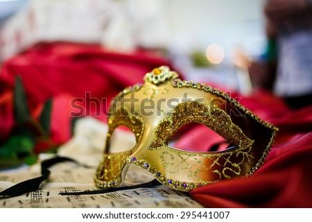 Female carnival mask laying on music sheet (close-up) - stock photo